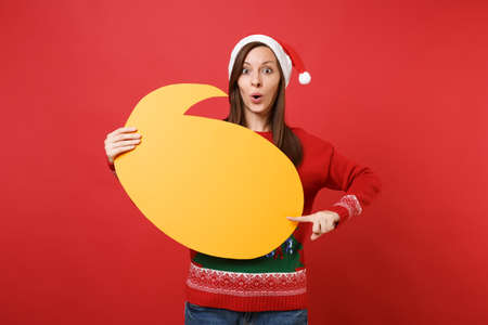 Shocked young Santa girl pointing index finger on yellow empty blank Say cloud speech bubble isolated on red wall background. Happy New Year 2019 celebration holiday party concept. Mock up copy space 写真素材