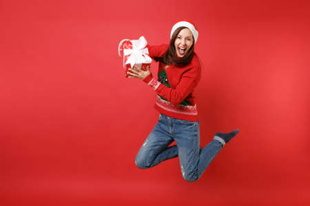 Crazy young Santa girl in Christmas hat jumping holding red box with gift, present screaming isolated on red wall background. Happy New Year 2019 celebration holiday party concept. Mock up copy space