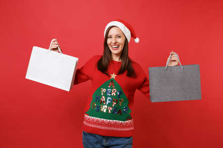 Joyful beautiful young Santa girl holding packages bags with purchases after shopping isolated on bright red wall background. Happy New Year 2019 celebration holiday party concept. Mock up copy space Stock Photo