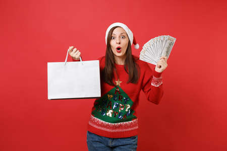Shocked young Santa girl hold lots bunch of dollars banknotes cash money, packages bags with purchases after shopping isolated on red background. Happy New Year 2019 celebration holiday party concept Stock Photo