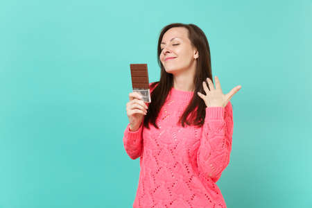 Stunning young woman in knitted pink sweater keeping eyes closed, hold in hands chocolate bar isolated on blue turquoise wall background, studio portrait. People lifestyle concept. Mock up copy space