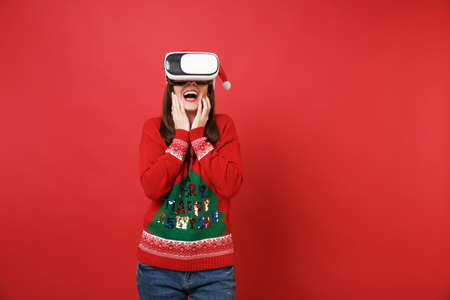 Amazed young Santa girl in knitted sweater, Christmas hat looking in headset, put hands on face isolated on red background. Happy New Year 2019 celebration holiday party concept. Mock up copy space