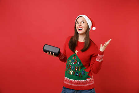 Stunning young Santa girl looking up, holding portable wireless music speaker isolated on bright red background. Happy New Year 2019 celebration holiday party concept. Mock up copy space 写真素材