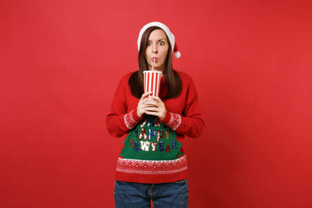 Shocked young Santa girl in knitted sweater, Christmas hat drinking cola or soda from plastic cup isolated on red background. Happy New Year 2019 celebration holiday party concept. Mock up copy space