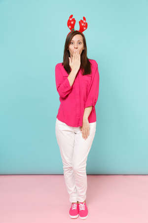 Full length portrait of fun young woman in rose shirt blouse, white pants, deer horns posing isolated on bright pink blue pastel wall background studio. Fashion lifestyle concept. Mock up copy space