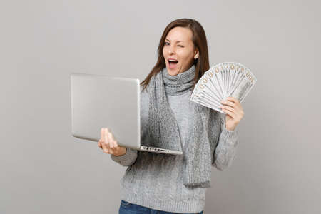 Blinking woman in sweater working on laptop pc computer, hold lots bunch of dollars banknotes cash money isolated on grey background. Healthy lifestyle online treatment consulting cold season concept 免版税图像
