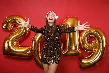Merry young Santa girl in shiny glitter dress, Christmas hat celebrating holiday party isolated on bright red wall background, golden numbers air balloons studio portrait. Happy New Year 2019 concept