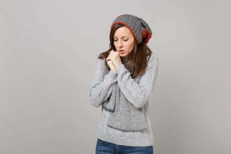 Young woman in gray sweater, hat and scarf with lowered head warming her hands isolated on grey background. Healthy fashion lifestyle, people sincere emotions, cold season concept. Mock up copy space