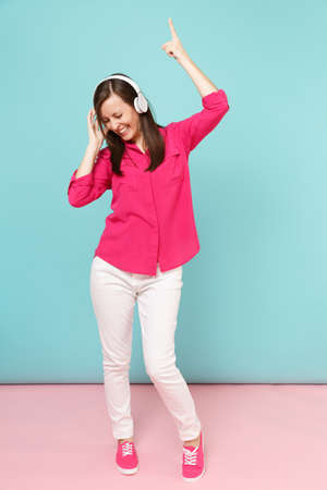 Full length portrait of young fun woman in rose shirt blouse, white pants, headphones dancing isolated on bright pink blue pastel wall background studio. Fashion lifestyle concept. Mock up copy space