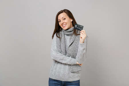 Attractive young woman in gray sweater scarf holding credit bank card isolated on grey background in studio. Healthy fashion lifestyle people sincere emotions, cold season concept. Mock up copy space