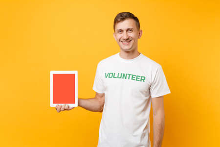 Man in white t-shirt written inscription green title volunteer hold tablet pc computer with blank empty screen isolated on yellow background. Voluntary free assistance help charity grace work concept Stock fotó
