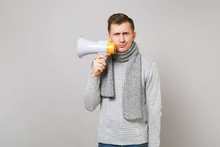Puzzled young man in gray sweater, scarf holding megaphone isolated on grey wall background, studio portrait. Healthy fashion lifestyle people sincere emotions cold season concept. Mock up copy space Stockfoto