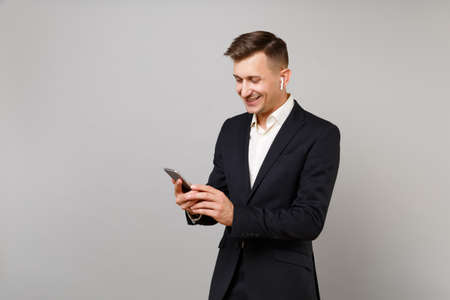 Smiling young business man in classic black suit with wireless earphones listening music using mobile phone isolated on grey background. Achievement career wealth business concept. Mock up copy space
