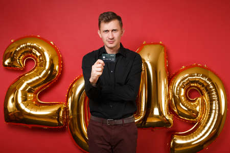 Merry young man in black shirt celebrating holiday party, holding credit card isolated on bright red wall background golden numbers air balloons studio portrait. Happy New Year 2019 Christmas concept