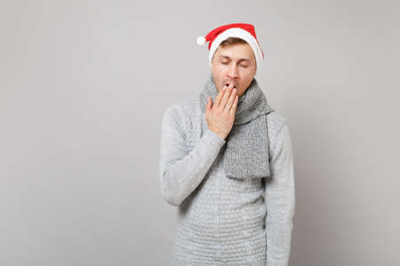 Sleepy Santa man in gray sweater scarf Christmas hat yawning, covering mouth with hand isolated on grey background in studio. Happy New Year 2019 celebration holiday party concept. Mock up copy space