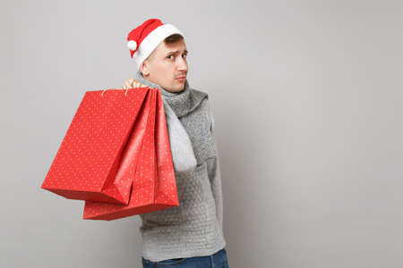 Young Santa man in Christmas hat holding red package bag with gifts, purchases after shopping isolated on grey background. Happy New Year 2019 celebration holiday party concept. Mock up copy space