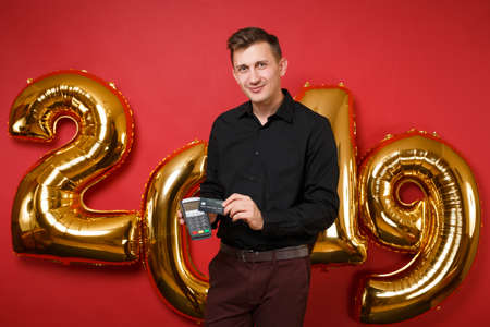 Man in black shirt celebrating holiday party holding bank payment terminal isolated on bright red wall background, golden numbers air balloons studio portrait. Happy New Year 2019 Christmas concept