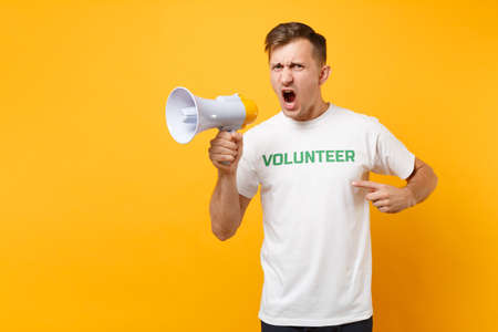 Portrait of man in white t-shirt written inscription green title volunteer scream in public address megaphone isolated on yellow background. Voluntary free assistance help, charity grace work concept