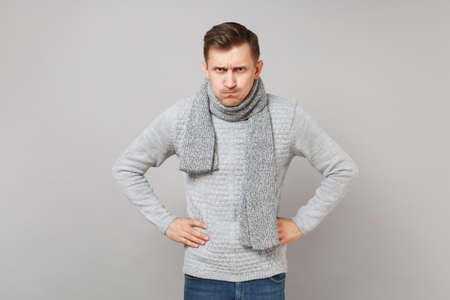 Strict young man in gray sweater, scarf standing with arms akimbo on waist isolated on grey wall background. Healthy fashion lifestyle people sincere emotions cold season concept. Mock up copy space