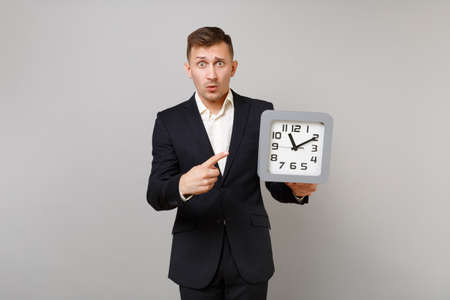 Shocked young business man in classic black suit, shirt pointing index finger on square clock in hand isolated on grey wall background. Achievement career wealth business concept. Mock up copy space Banque d'images - 114029151