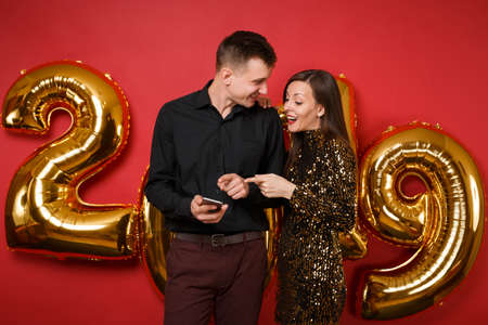 Couple guy girl in dress black shirt celebrating holiday party hold cellphone isolated on bright red wall background golden numbers air balloons studio portrait. Happy New Year 2019 Christmas concept