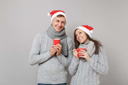 Fun couple girl guy in red Santa Christmas hat gray sweaters scarves hold cups of tea isolated on grey wall background, studio portrait. Happy New Year 2019 holiday party concept. Mock up copy space