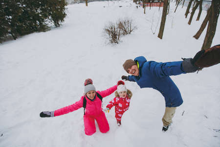 Funny family man, woman and little girl in warm clothes playing, making snowman spreading hands in park or forest outdoors. Winter fun, leisure on holidays. Love relationship family lifestyle concept