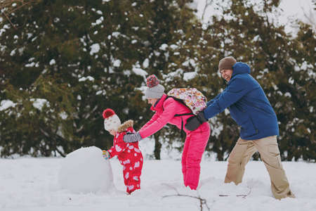 Family woman, man little girl in warm clothes playing, making snowman, pushing each other in snowy park or forest outdoors. Winter fun, leisure on holidays. Love relationship family lifestyle concept