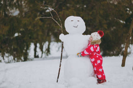 Pretty little girl in winter warm clothes and hat playing, hugging with snowman in snowy park or forest outdoors. Winter fun, leisure on holidays. Love relationship family childhood lifestyle concept