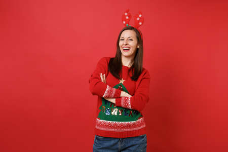 Joyful young Santa girl in knitted sweater fun decorative deer horns on head holding hands folded isolated on red background. Happy New Year 2019 celebration holiday party concept. Mock up copy space 版權商用圖片