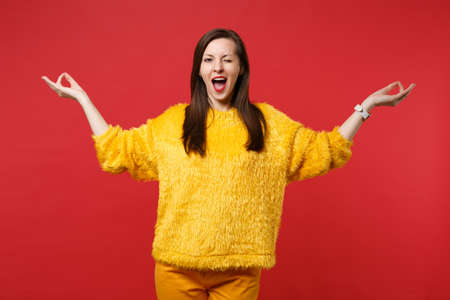 Funny young woman in yellow fur sweater blinking hold hands in yoga gesture keeping mouth wide open isolated on red background in studio. People sincere emotions lifestyle concept. Mock up copy space 写真素材