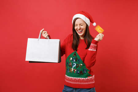 Joyful young Santa girl keeping eyes closed, holding credit card, packages bags with purchases after shopping isolated on bright red background. Happy New Year 2019 celebration holiday party concept