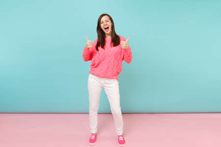 Full length portrait of smiling young woman in knitted rose sweater, white pants posing isolated on bright pink blue pastel wall background in studio. Fashion lifestyle concept. Mock up copy space Stock fotó