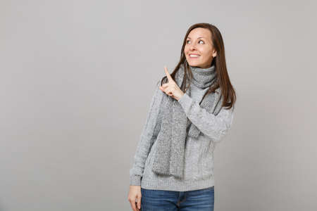 Smiling young woman in gray sweater, scarf looking up, pointing index finger aside isolated on grey wall background. Healthy fashion lifestyle people emotions, cold season concept. Mock up copy space