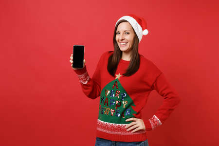 Beautiful young Santa girl in Christmas hat holding mobile phone with blank empty screen isolated on bright red background. Happy New Year 2019 celebration holiday party concept. Mock up copy space Stock fotó