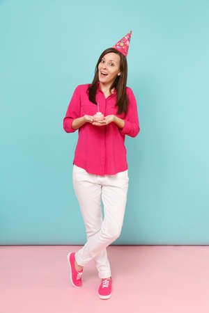 Full length portrait woman in rose shirt blouse, white pants, birthday hat with cake posing isolated on bright pink blue pastel wall background studio. Fashion lifestyle concept. Mock up copy space 写真素材