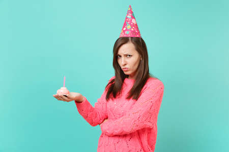 Offended upset young woman in knitted pink sweater, birthday hat hold in hand cake with candle isolated on blue turquoise wall background studio portrait. People lifestyle concept. Mock up copy space