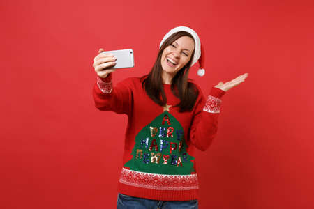 Joyful Santa girl in Christmas hat doing taking selfie shot on mobile phone, pointing hand aside isolated on red background. Happy New Year 2019 celebration holiday party concept. Mock up copy space