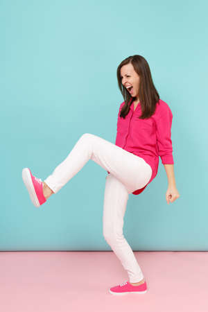 Full length portrait of angry fun young pretty woman in rose shirt blouse, white pants posing isolated on bright pink blue pastel wall background studio. Fashion lifestyle concept. Mock up copy space Archivio Fotografico