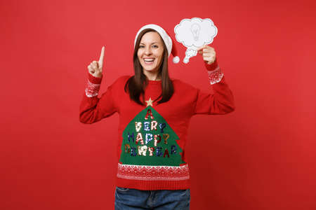 Joyful young Santa girl pointing index finger up, holding say cloud with lightbulb, idea isolated on bright red background. Happy New Year 2019 celebration holiday party concept. Mock up copy space
