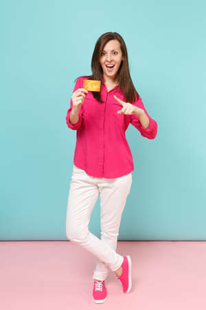 Full length portrait of smiling young woman in rose shirt blouse white pants hold credit card isolated on bright pink blue pastel wall background studio. Fashion lifestyle concept. Mock up copy space 写真素材