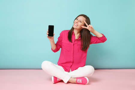 Full length portrait of young fun woman in rose shirt white pants sit on floor hold cellphone isolated on bright pink blue pastel wall background studio. Fashion lifestyle concept. Mock up copy space