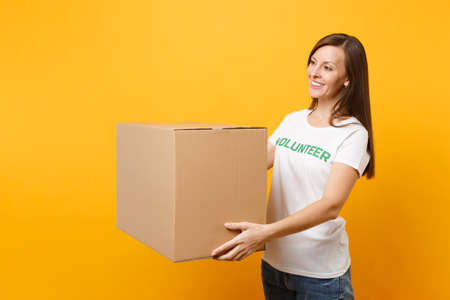 Portrait of smiling woman in white t-shirt with written inscription green title volunteer with big cardboard box isolated on yellow background. Voluntary free assistance help, charity grace concept