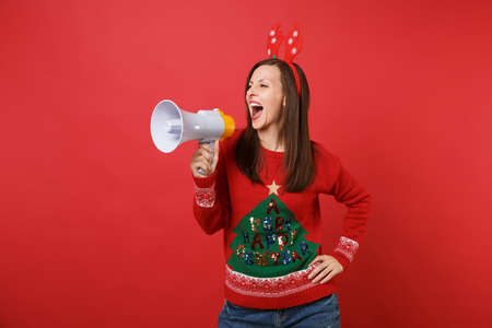 Emotional young Santa girl in fun decorative deer horns on head screaming on megaphone isolated on bright red background. Happy New Year 2019 celebration holiday party concept. Mock up copy space Stockfoto