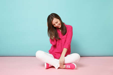 Full length portrait of smiling young woman in rose shirt blouse, white pants sitting on floor isolated on bright pink blue pastel wall background studio Fashion lifestyle concept. Mock up copy space
