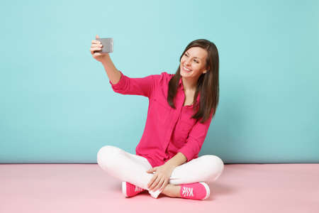 Full length woman in rose shirt, white pants sitting on floor doing selfie shot on cellphone isolated on bright pink blue pastel wall background studio. Fashion lifestyle concept. Mock up copy space