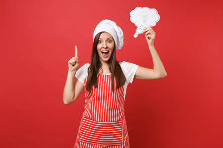 Housewife female chef cook or baker in striped apron white t-shirt toque chefs hat isolated on red wall background. Fun housekeeper woman hold cloud with lightbulb idea. Mock up copy space concept