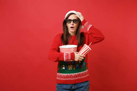 Bewildered young Santa girl in 3d glasses watching movie film, holding popcorn, cup of soda isolated on red background. Happy New Year 2019 celebration holiday party concept. Mock up copy space