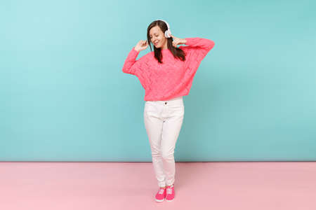 Full length portrait of happy young woman in knitted rose sweater, white pants, headphones isolated on bright pink blue pastel wall background in studio. Fashion lifestyle concept. Mock up copy space Stock fotó