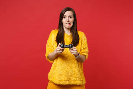 Portrait of concerned young woman in yellow fur sweater biting lips, playing video game with joystick isolated on bright red background. People sincere emotions, lifestyle concept. Mock up copy space Banque d'images